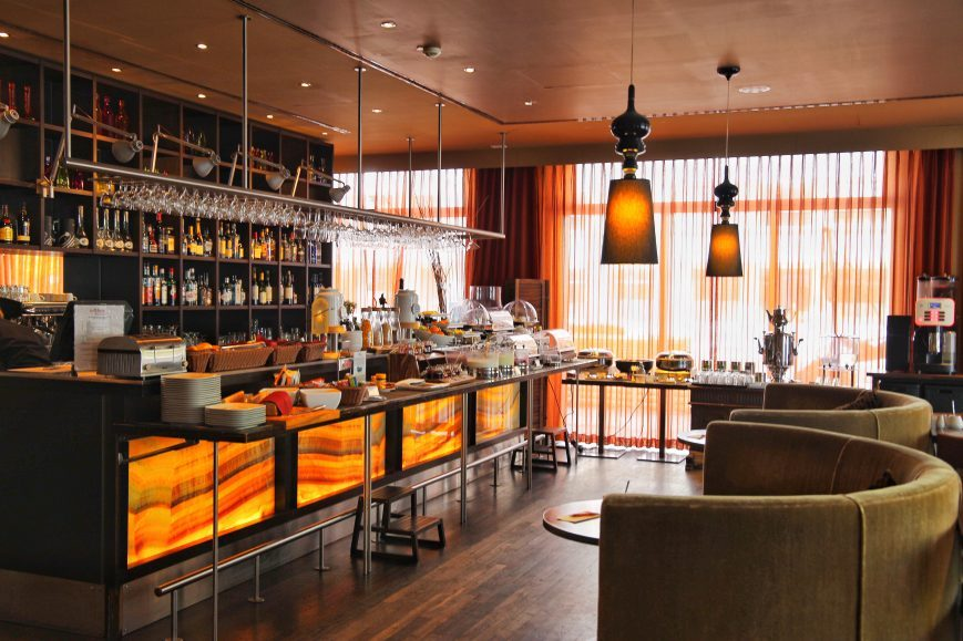 Adina Apartment Hotel,grey couch, orange painting, berlin, checkpoint charlie, breakfast, orange, bar